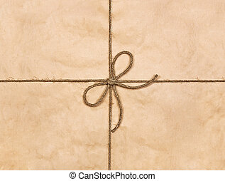 String tied in a bow on a brown recycled paper