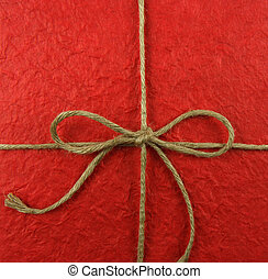 String tied in a bow on red paper
