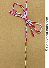 String tied in a bow, over brown paper packaging.