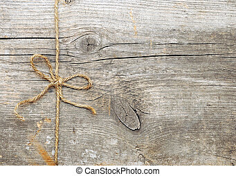String tied in a bow, over old wood