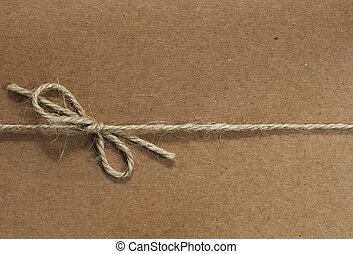 String tied in a bow, over brown recycled paper. Great textures in the twine and paper.