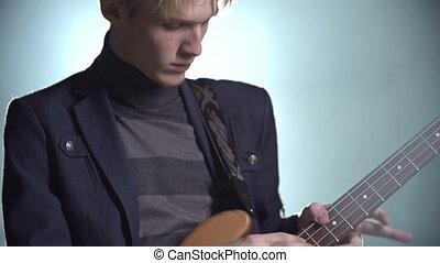 String-Whanger - Tilt of sexy blond axeman plucking strings...