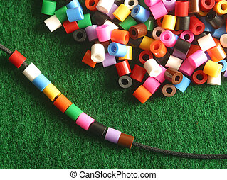 stringing beads - Stringing colorful plastic beads.