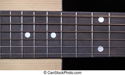 Strings of acoustic guitar, vibration, on black, close up -...