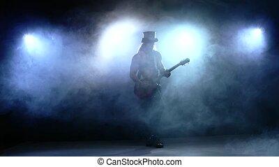 Strip man playing bass guitar in studio, Slow motion, smoke