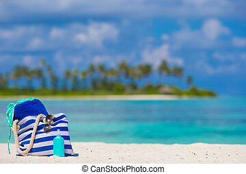 Stripe bag, blue towel, sunglasses, sunscreen bottle and ...