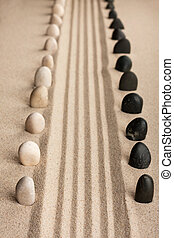 Stripe of white and black stones sticking of the sand