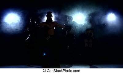 Stripease policeman: four person dancing, on dark