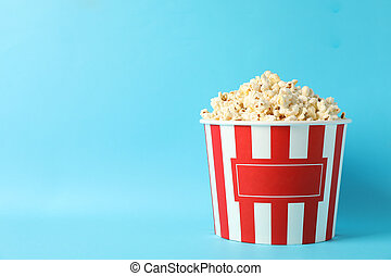 Striped bucket with popcorn on blue background, space for text