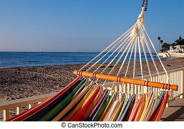 Colorful stripy hammock hanging on a verandah overlooking a blue ocean.