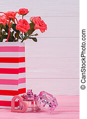 Striped shopping bag with rose flowers and perfume bottle.