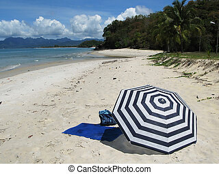 Striped umbrella on a secluded beach of Langkawi island,...