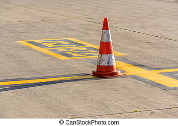 Striped white orange traffic cone stands on airport runway, sunny summer day