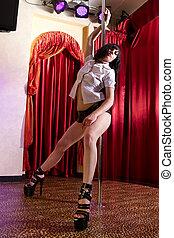 Stripper dancing on pole - Strip tease dancer posing at the...