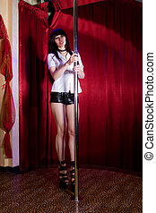 Stripper girl pole dancing on stage
