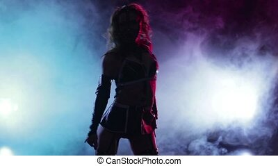 Stripper in leather clothes performs sexy dance on smoke scene