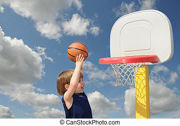Striving - A little boy reaches up to put his basketball in...
