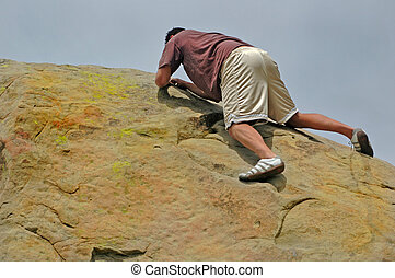 Striving - Man struggles to reach top of rock