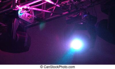 strobe lights emitting different color beams hanging under...