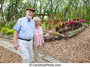 Stroll in the Park - Happy senior couple taking an afternoon...