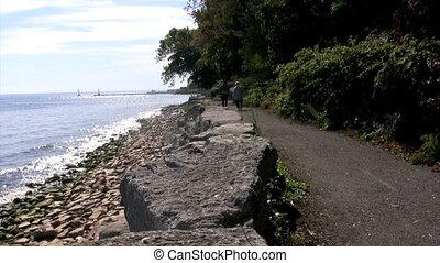 older couple walks along rocky shore