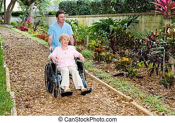 Stroll Through the Garden - Nursing home orderly pushing a...