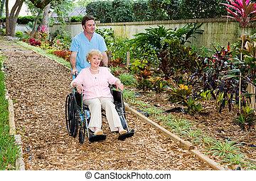 Stroll Through the Garden - Nursing home orderly pushing a...