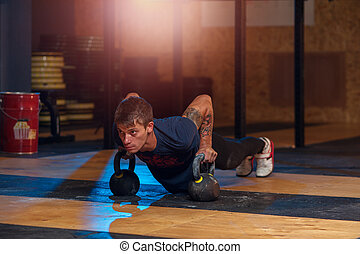 Strong adult exercising with kettle bell in gym