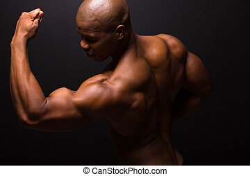 strong african american bodybuilder posing on black...