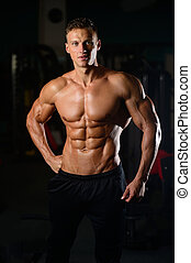 Strong athletic man fitness model showing six pack abs -...