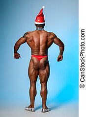 Strong athletic man in a santa hat back
