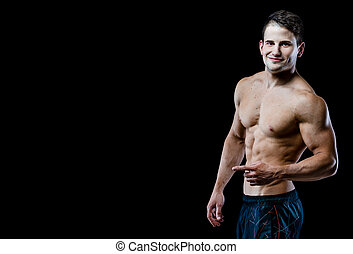 Strong Athletic Man showing muscular body and sixpack abs over black background