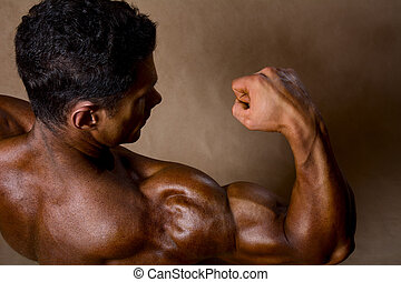 Strong athletic man shows biceps. View top athlete