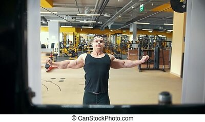 Strong athletic man training in a workout room