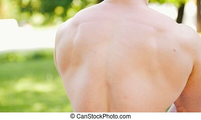 Strong athletic man with muscular torso warming up in the park