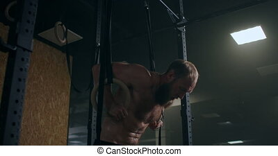 Strong bearded male athlete performs push-ups on gym rings in slow motion in the gym. High quality 4k footage