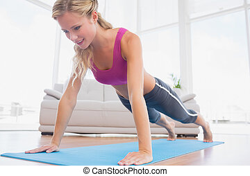 Strong blonde in plank position on exercise mat at home in...