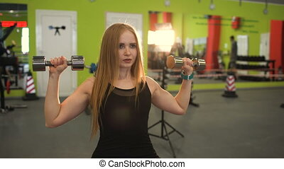 Strong blonde woman doing exercise wtiht lifting weights in fitnest club