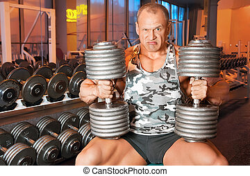 strong bodybuilder training muscles in gym