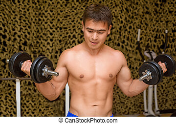 strong bodybuilder training muscles in gym, training bicepses