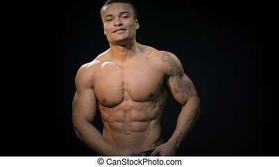 Strong bodybuilder with six pack, perfect abs, shoulders, biceps, triceps and chest. Muscular man bodybuilder. Man posing on a black background, shows his muscles. Bodybuilding, posing, black background, muscles - the concept of bodybuilding. Article about bodybuilding.