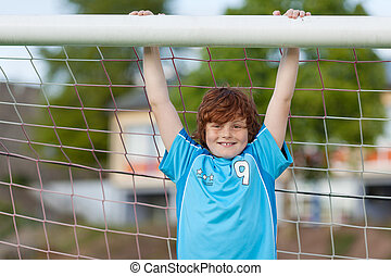 strong boy hanging on soccer goal
