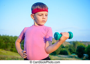 Strong Boy in an Outdoor Exercise Lifting Dumbbell