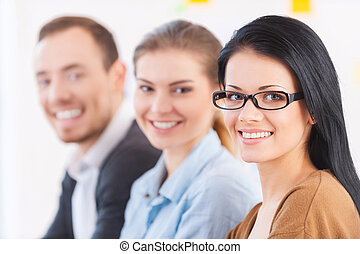 Strong business team. Three cheerful young colleagues sitting together at their working place and smiling at camera