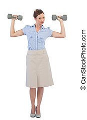 Strong businesswoman posing with dumbbells looking at camera