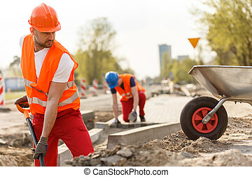 Strong construction worker digging