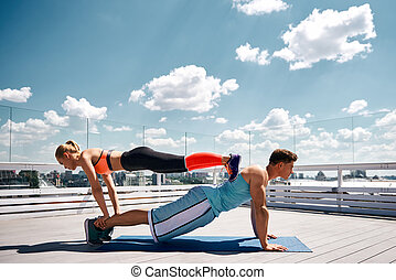 Strong couple is jointly planking on terrace - Ripped guy...