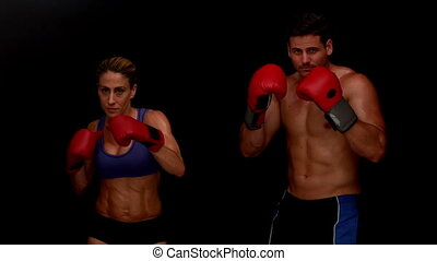 Strong couple punching towards camera together in slow...