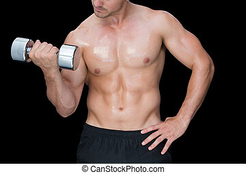 Strong crossfitter lifting up heavy dumbbell on black...