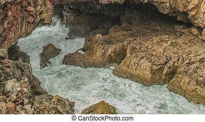 Strong extreme waves crash into grotto cliff cave, Boca do Inferno, Portugal